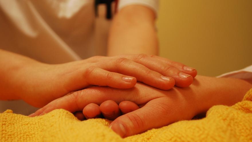 Unas manos jóvenes cogen una mano de persona mayor