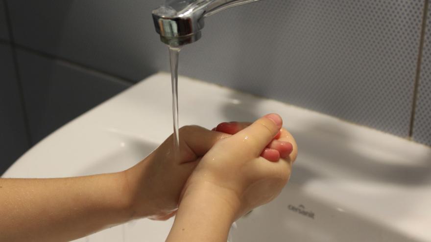 manos de niño lavandoselas en un lavabo