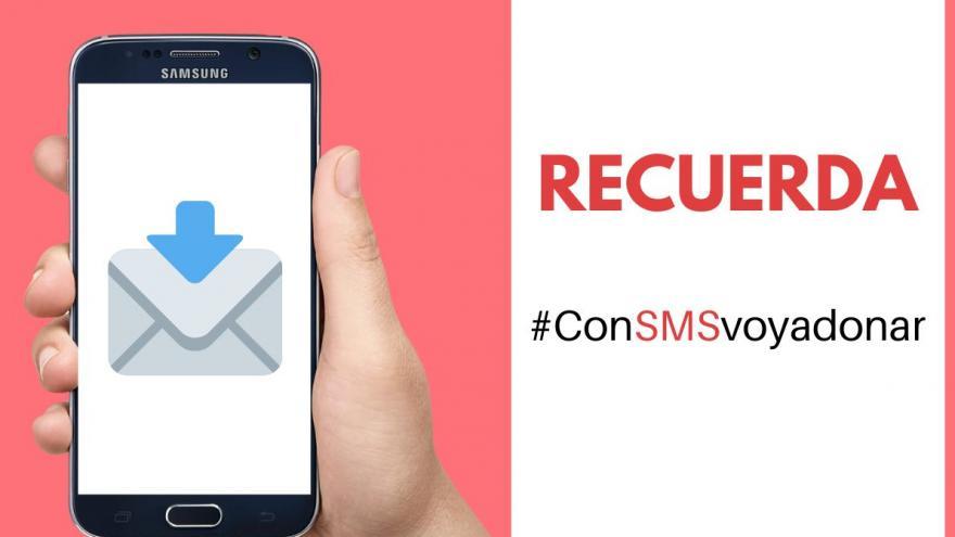 Imágen de mano con móvil y hashtag #onSMSvoyadonar