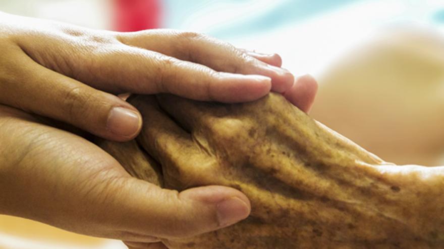 Manos de cuidadora y manos de anciano