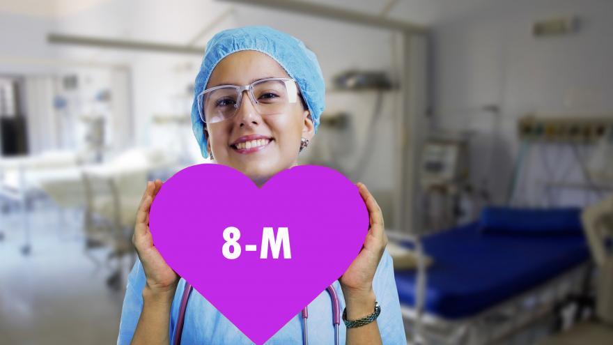 Sanitaria sujetando un corazón morado en el que pone 8M
