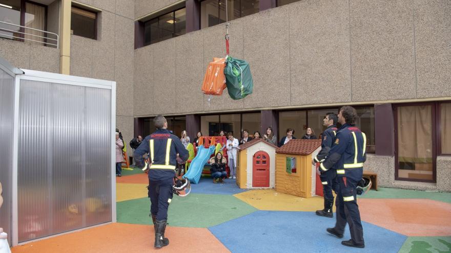 Bomberos bajan regalos en rappel a los niños del Hospital de Getafe