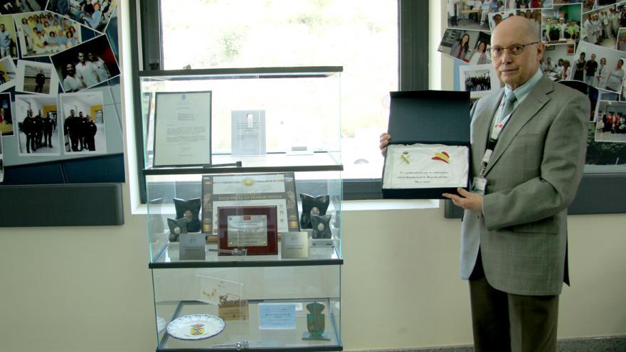 El Director Gerente, Carlos Sangregorio, coloca la placa en la vitrina de trofeos del Hospital