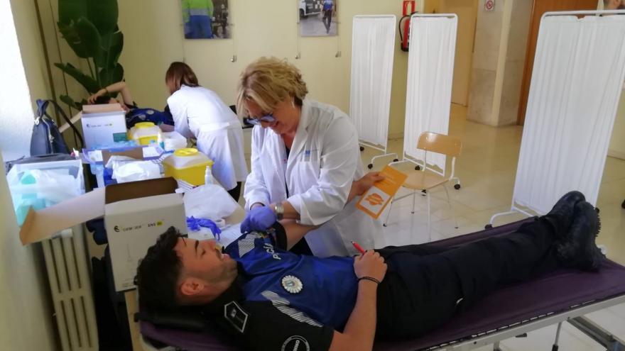 Enfermera extrayendo tubos de sangre a policía