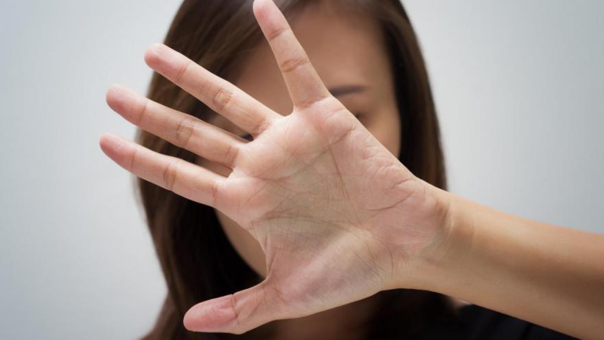 Una mujer se tapa la cara con la mano