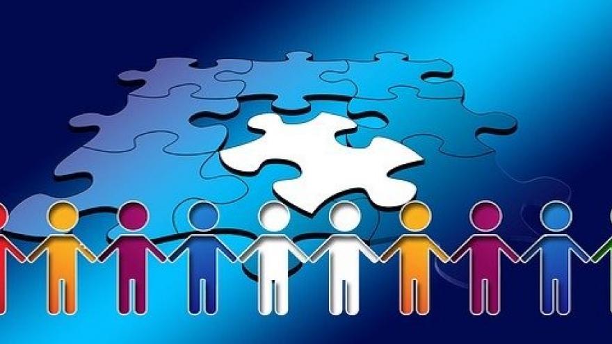 Personas de la mano haciendo un puzle, trabajando y aprendiendo en común