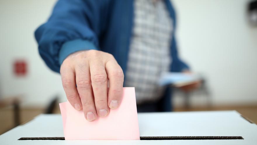 Votante introduciendo su papeleta en la urna