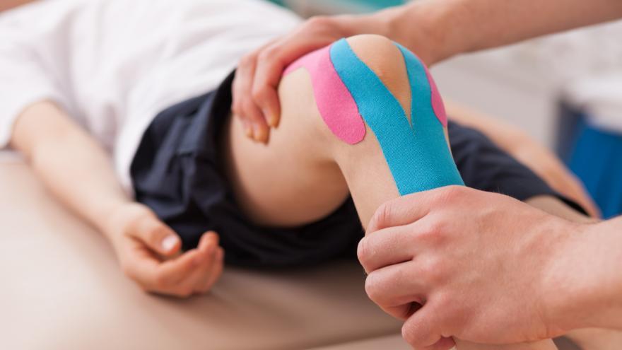 Fisioterapeuta tratando la rodilla de un paciente