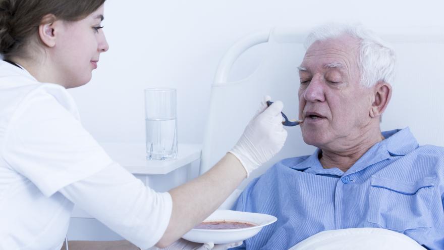 Profesional dando de comer a un paciente