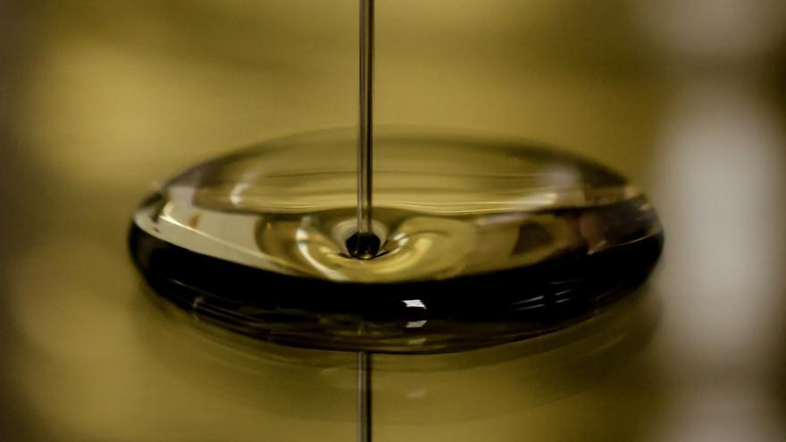Chorro de aceite de oliva cayendo sobre un recipiente con aceite