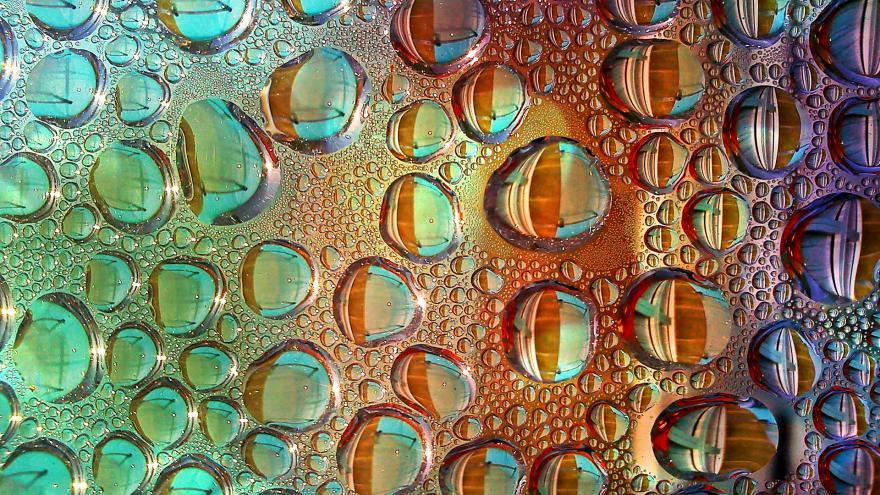 Gotas de agua sobre un cristal y fondo de distintos colores