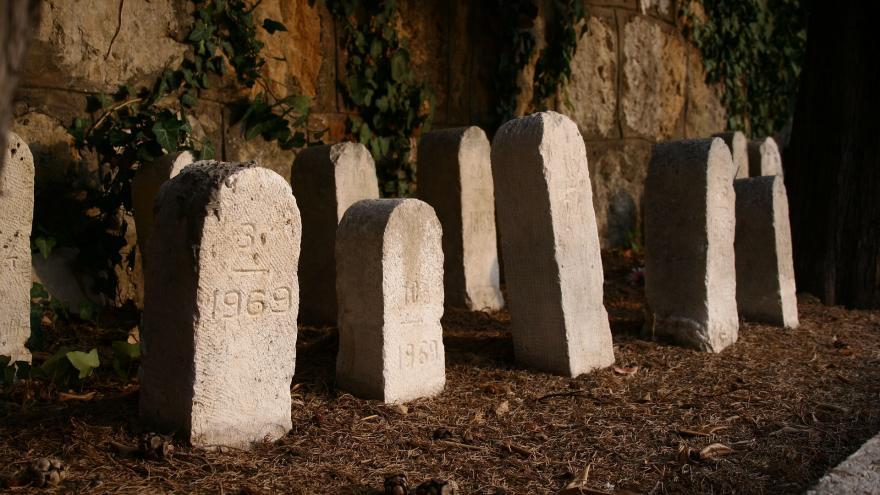 Lápidas sencillas frente a la pared de un cementerio