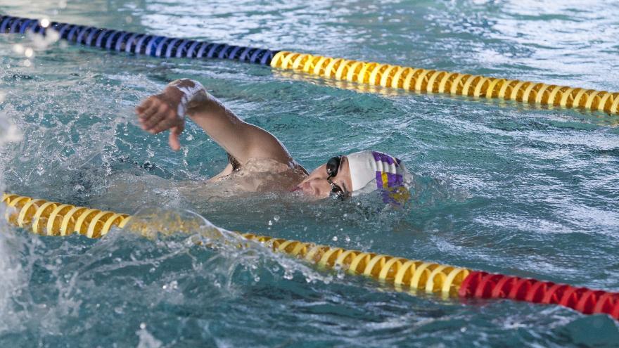 Imagen de nadador con gorro y gafas entre corcheras en una piscina