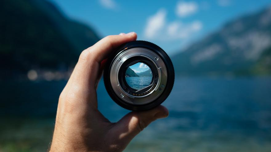 Imagen de una mano sosteniendo un objetivo fotográfico a través del cual se ve un lago