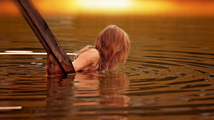Chica entrando por unas escaleras en el agua de una zona de baño al atardecer