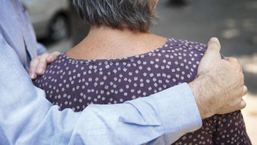 Mujer mayor junto a hombre que la lleva por los hombros