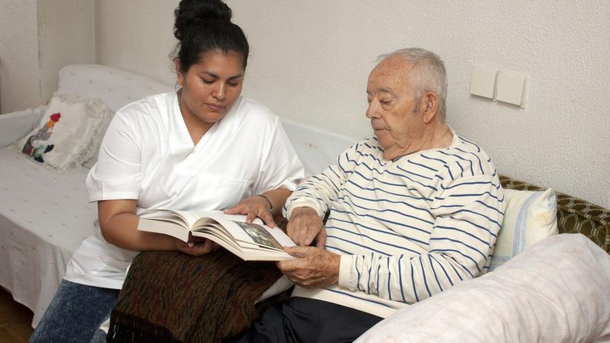 Hombre mayor y cuidadora sentandos