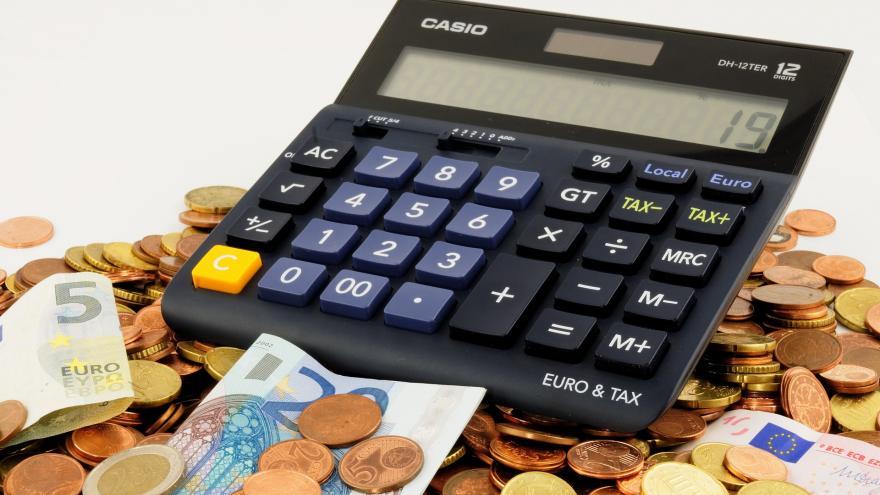 Imagen de una calculadora, varias monedas y billetes