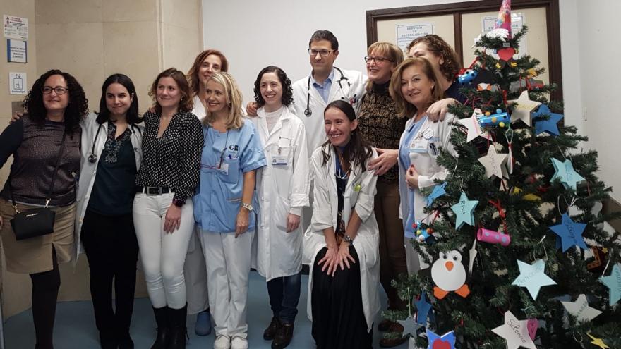 Profesionales del Servicio de Oncología del Hospital de Móstoles posan tras decorar el árbol de Navidad