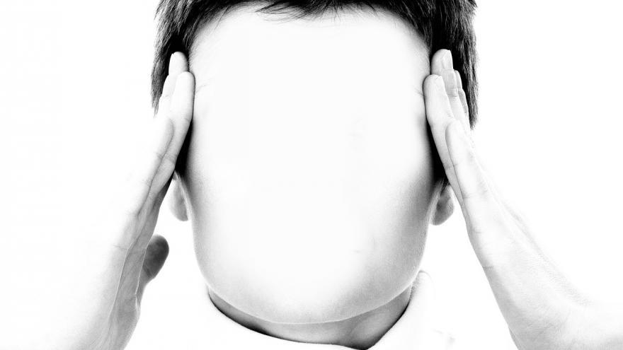 Una silueta coloca sus dos manos en la cabeza