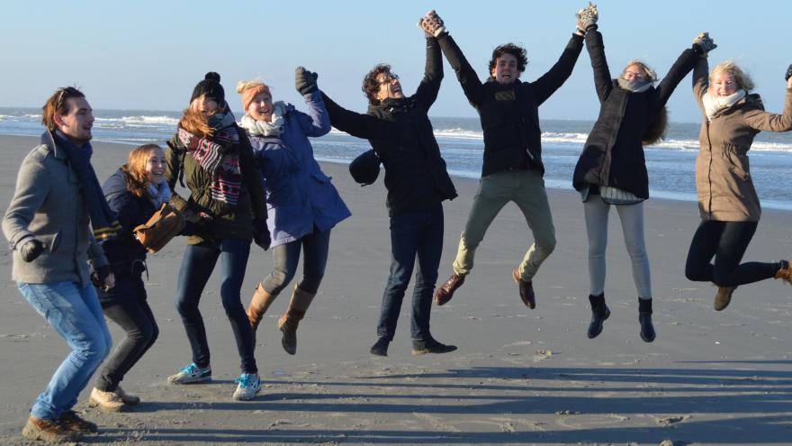 Jóvenes de manos dadas saltando en una playa