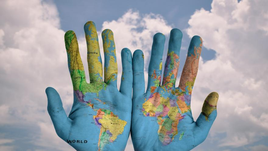 Mapamundi sobre unas manos abiertas