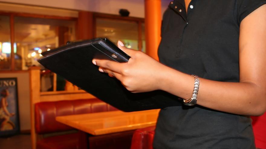 Camarera con una carta de menú en la mano