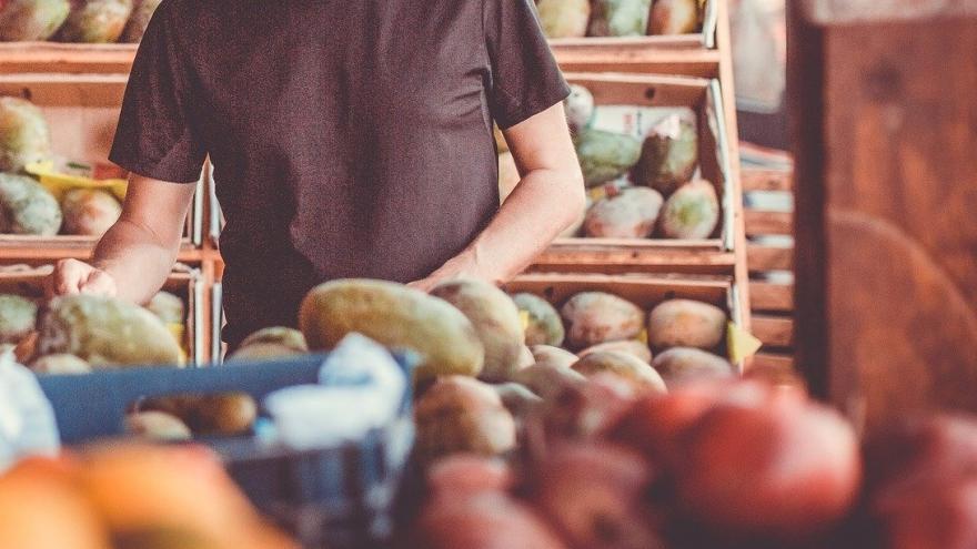 Un hombre coge frutas en una tienda