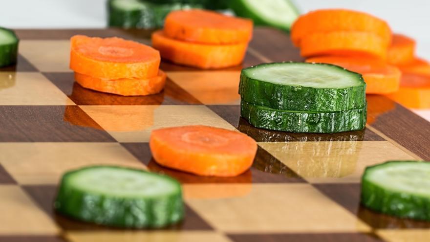 Imagen de un tablero de damas con rodajas de calabacín y zanahorias en lugar de fichas