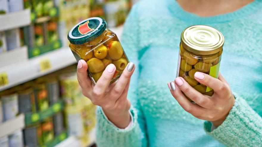 Mujer comparando dos botes de aceitunas en un supermercado