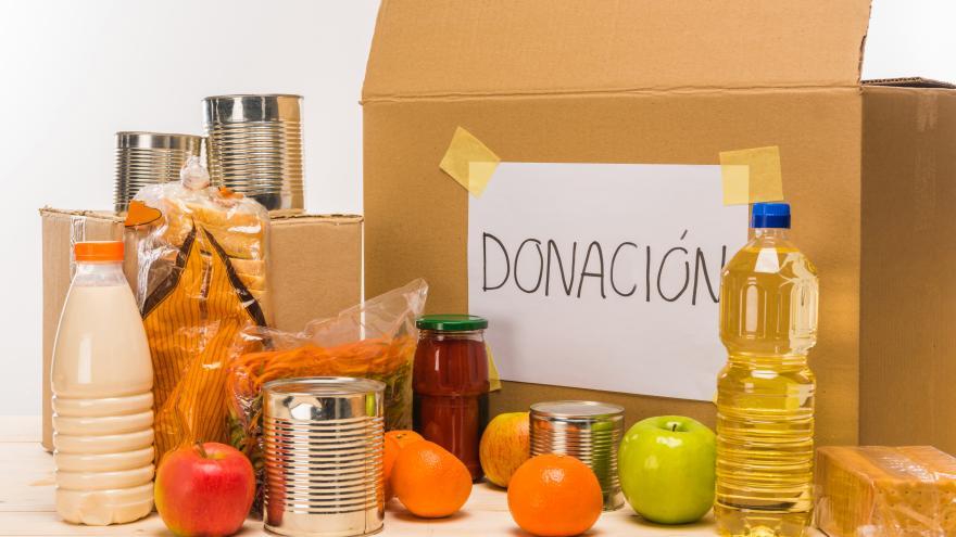 """Caja con un cartel donde se lee """"donación junto a diferentes alimentos"""