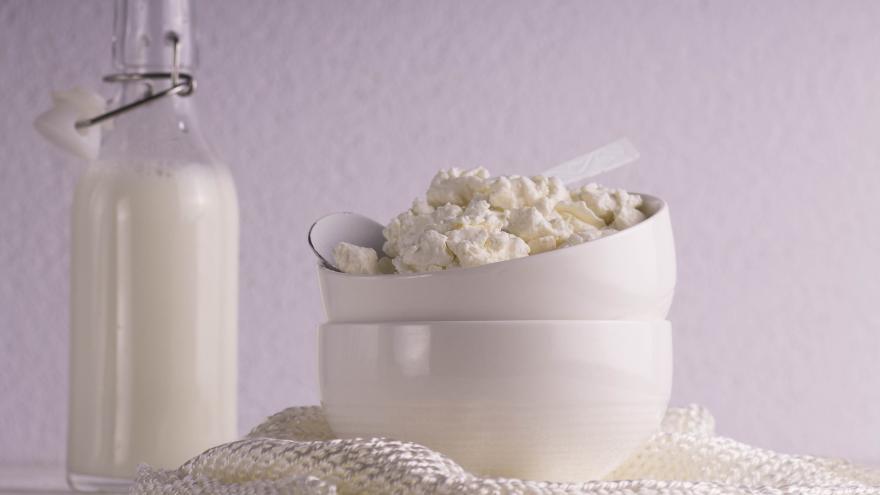 Una botella transparente con leche a la izquierda y un bowl con requesón