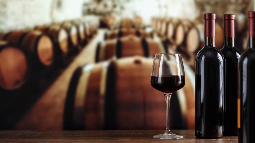 Copas de llenas de vino en una bodega con barricas de madera