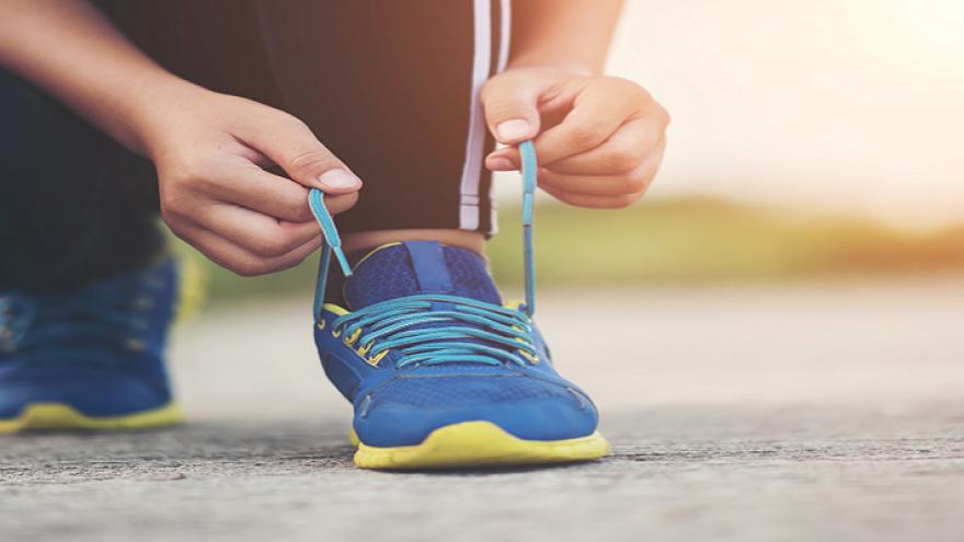 Persona agachada atándose los cordones de su zapatilla de deporte