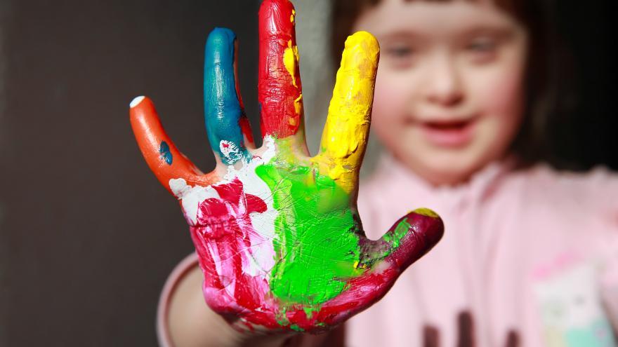 Una niña con Síndome de Down con una mano pintada de muchos colores extendida hacia la cámara