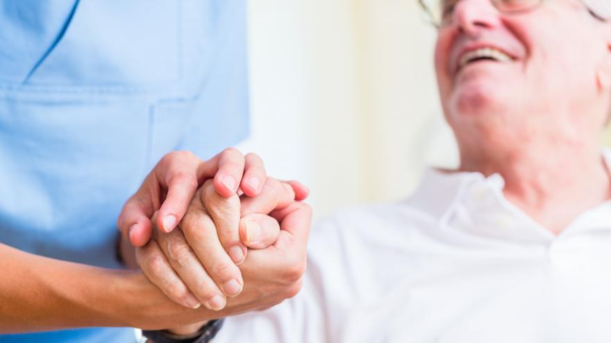 Una enfermera coge la mano de un anciano que le responde con una sonrisa