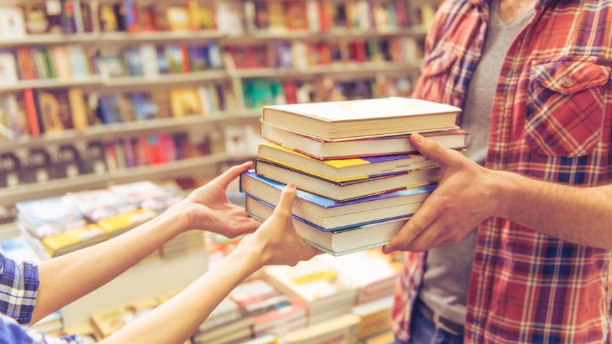 Niño cogiendo libros que le ofrecen en una biblioteca