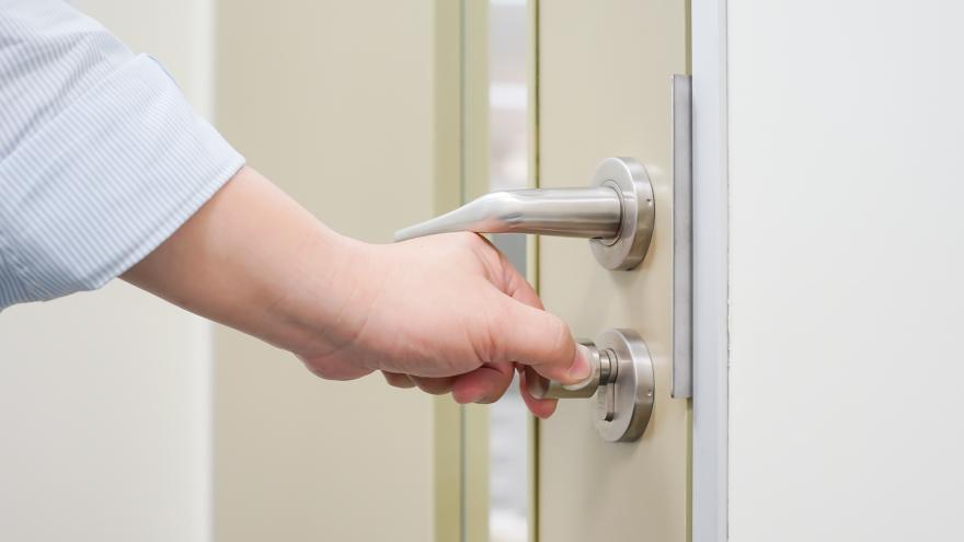 Una mano abre con una llave la puerta de una vivienda