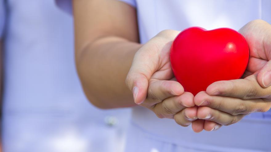manos con un corazón de juguete