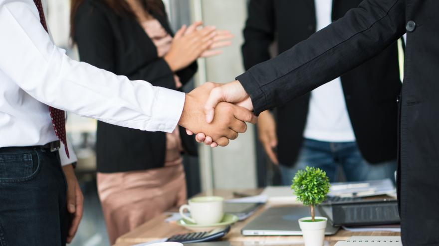 Dos hombres trajeados se dan la mano sellando un acuerdo