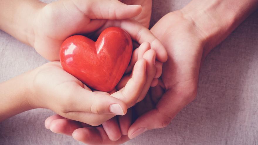 Dos manos le dan un corazón de juguete a otras dos manos representando una donación