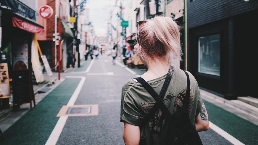 Chica caminado por la calle con una mochila