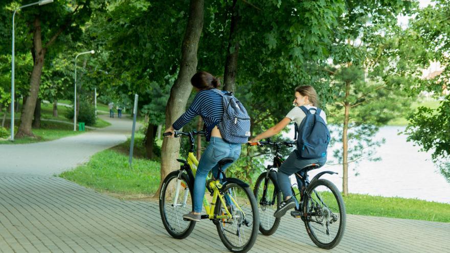 Dos chicas en bici por zona ajardinada