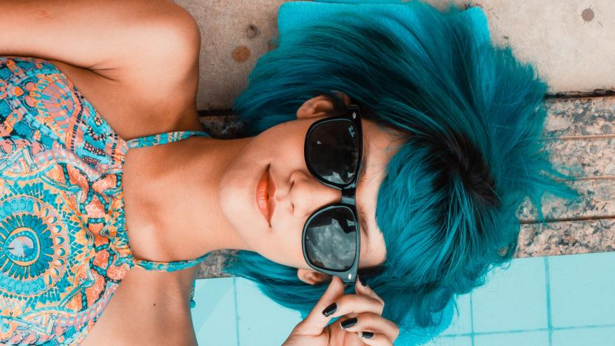 Primer plano de cara de una chica con gafas de sol y pelo azul