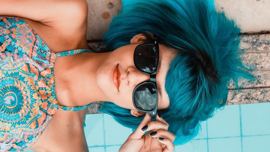 Primer plano de chica con pelo azul y gafas de sol