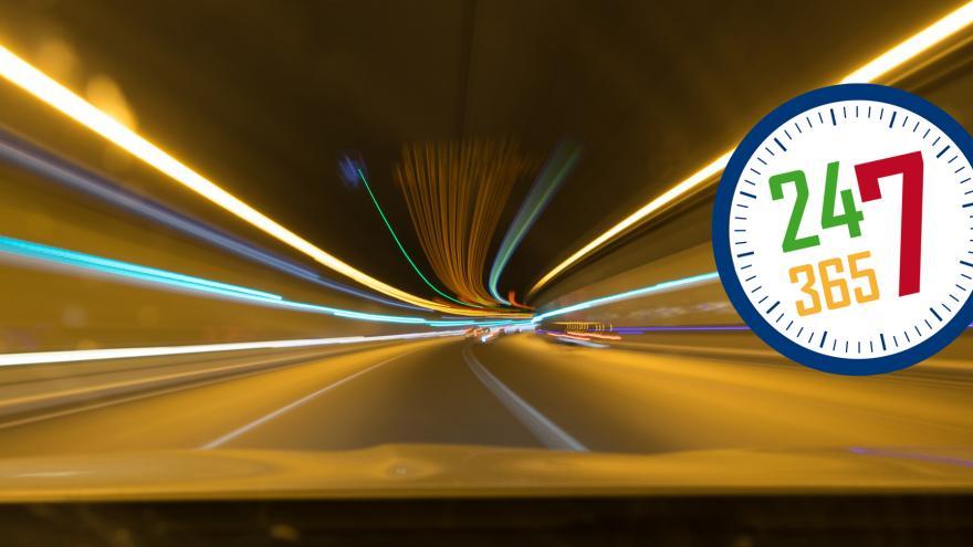 Imágen de luces en un túnel con un vector en forma de reloj con los número 24 en color rojo, 7 en color azul, 365 en color verde