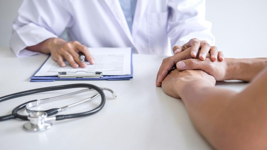 Médico sosteniendo la mano a un paciente