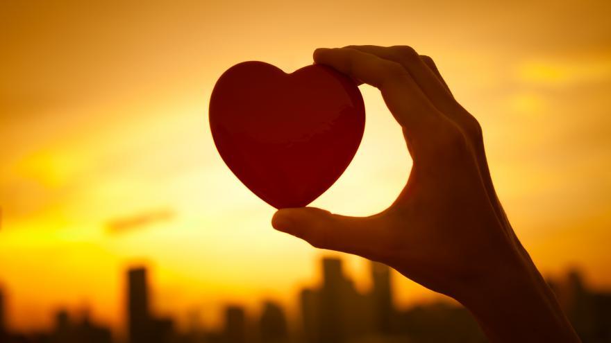 Mano sosteniendo un corazón contra una puesta de sol en la ciudad