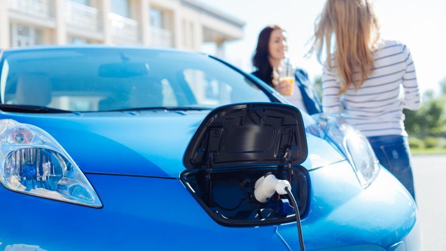 Dos mujeres apoyadas en un coche eléctrico azul mientras este se carga