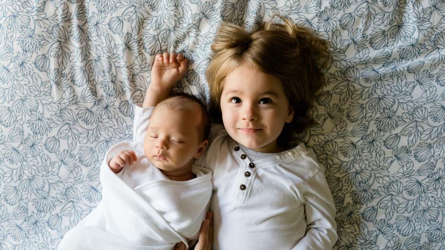 Bebé con su hermana encima de una cama